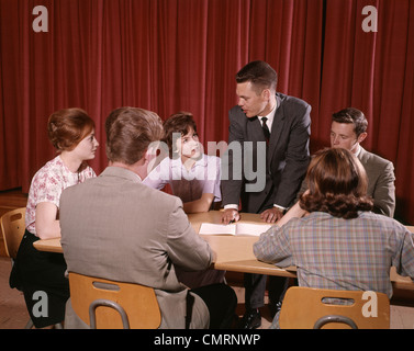 1960s GROUP OF SIX STUDENTS SITTING AT AROUND A TABLE TALKING THREE BOYS THREE GIRLS TEENAGE INDOOR - Stock Photo