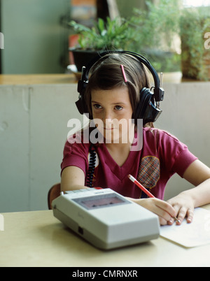 1980s LITTLE GIRL DOING HOMEWORK LISTENING TO  AUDIO CASSETTE TAPE - Stock Photo