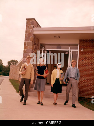 1960 1960s 4 STUDENTS WALKING OUT SCHOOL BUILDING TEENS TEENAGERS HIGH SCHOOL COLLEGE BOYS GIRLS STUDENT EDUCATION - Stock Photo