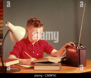 1960 1960s BOY LISTENING RADIO STUDYING STUDY HOMEWORK BOYS LISTEN RADIOS BOOK BOOKS LAMP SCHOOL CHILDREN CHILD - Stock Photo