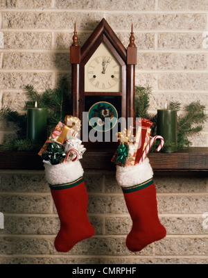 1970s CHRISTMAS STILL LIFE ANTIQUE FIREPLACE MANTLE CLOCK STOCKINGS FULL OF PRESENTS CANDY CANES - Stock Photo