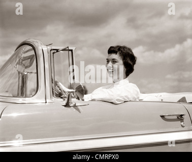 1950s SMILING WOMAN DRIVING CHEVROLET CONVERTIBLE AUTOMOBILE - Stock Photo