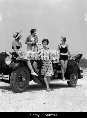 1920s 1930s FOUR WOMEN IN DRESSES AND BATHING SUITS GATHERED AROUND CONVERTIBLE TOURING CAR AT SEASHORE BEACH - Stock Photo