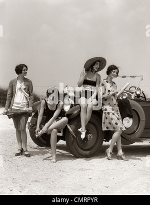 1920s GROUP OF FOUR WOMEN AT SHORE GATHERED AROUND CONVERTIBLE TWO IN DRESSES & TWO IN BATHING SUITS - Stock Photo
