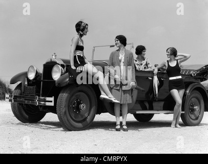 1920s 1930s FOUR WOMEN AROUND CONVERTIBLE TOURING CAR AT SEASHORE TWO IN BATHING SUITS & TWO DRESSED FOR FASHION - Stock Photo