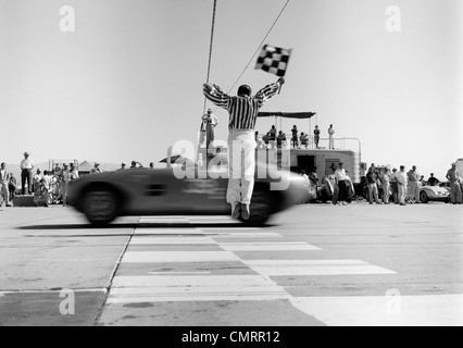 1960s MAN JUMPING WAVING CHECKERED FLAG AS WINNING SPORTS CAR CROSSING THE FINISH LINE - Stock Photo