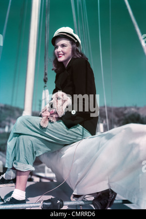 1940s 1950s SMILING WOMAN WEARING SAILING YACHTING OUTFIT SITTING ON EDGE OF SAILBOAT HOLDING PUPPY IN LAP - Stock Photo