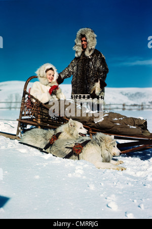 1940s 1950s COUPLE WEARING FUR LINED PARKAS WOMAN SITTING IN DOG SLED NEXT TO TWO DOGS HUSKIES - Stock Photo