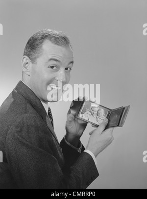 1950s 1960s MAN SMILING HOLDING  WALLET SHOWING PHOTO OF FAMILY LOOKING AT CAMERA - Stock Photo