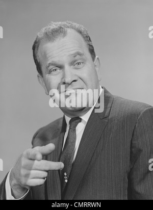 1950s 1960s PORTRAIT MAN WEARING SUIT TIE SMILING POINTING FINGER LOOKING AT CAMERA - Stock Photo