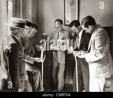 1930s BROKERS BUSINESSMEN READING TICKER TAPE AS IT COMES OUT OF GLASS DOMED MACHINE - Stock Photo