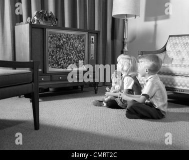 1960s BROTHER & SISTER SITTING ON LIVING ROOM FLOOR WATCHING TV - Stock Photo