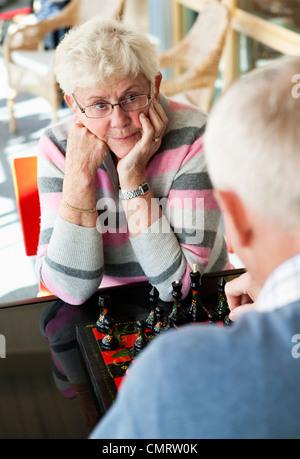 Seniors playing board-game - Stock Photo