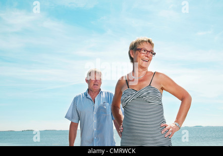 Man and woman standing on the beach - Stock Photo