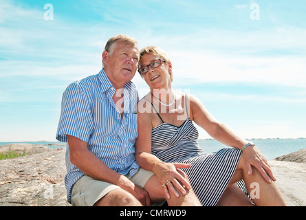 Two elderly people sitting on the beach - Stock Photo