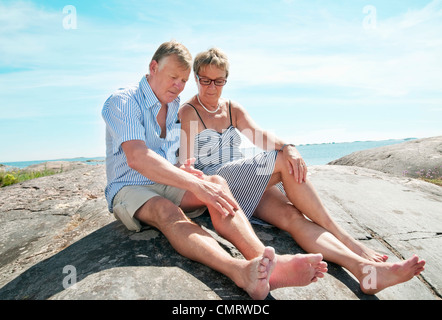 Couple sitting on a rock - Stock Photo