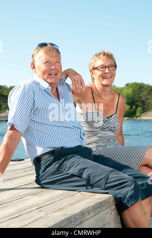 Two people sitting on pier by the water - Stock Photo