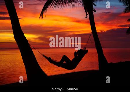 Woman in hammock, and palm trees at sunset, Coral Coast, Viti Levu, Fiji, South Pacific - Stock Photo
