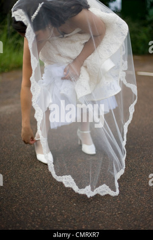 Woman in a wedding-dress standing outdoors - Stock Photo