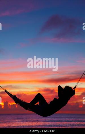 Woman in hammock at sunset, Coral Coast, Viti Levu, Fiji, South Pacific - Stock Photo