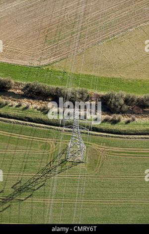 Aerial view of an electricity pylon and power lines crossing a stream - Stock Photo