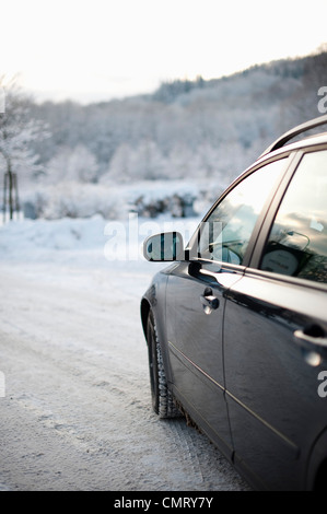 A car on a snow-covered gravel road - Stock Photo