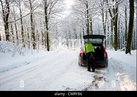 Man packing boot on winter road - Stock Photo