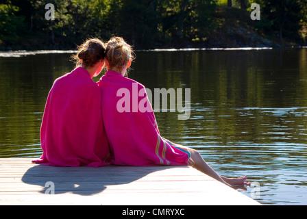 Rear view of teenage girls on sitting on pier