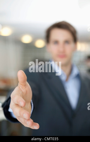 Businessman with his hand outstretched in greeting - Stock Photo