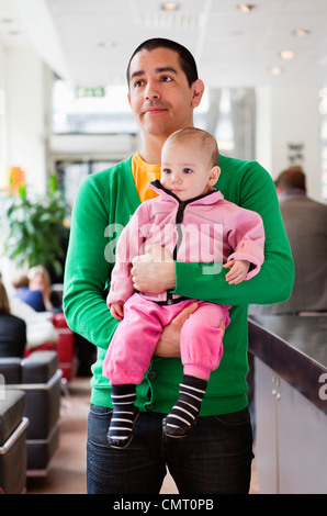 Father holding daughter (0-11 months) in his arms - Stock Photo