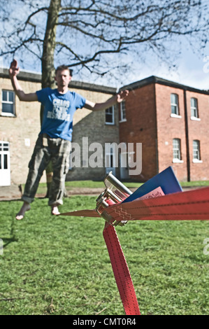 A performer practising on a slackline - Stock Photo