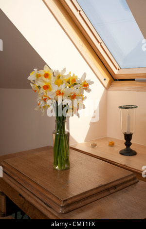 Daffodils in a vase on a table under a skylight. - Stock Photo