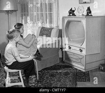 1950s BOY AND GIRL WATCHING TV IN LIVING ROOM - Stock Photo
