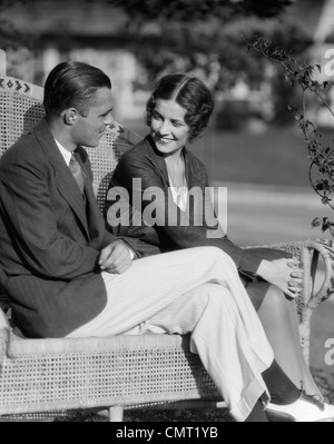 1930s SMILING COUPLE SITTING TOGETHER ON WICKER BENCH HUSBAND WIFE OUTDOOR - Stock Photo