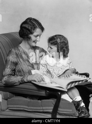 1920s 1930s MOTHER & DAUGHTER SMILING SITTING IN CHAIR READING BOOK - Stock Photo