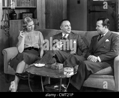 1930s 1940s TWO MEN AND ONE WOMAN SOCIAL GROUP SITTING ON COUCH SMOKING CIGARETTES TALKING - Stock Photo