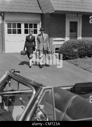 1950s COUPLE CARRYING LUGGAGE WALKING TOWARDS CONVERTIBLE CAR IN DRIVEWAY - Stock Photo