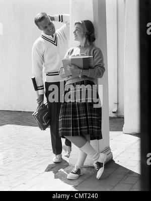 1950s 1960s COLLEGE HIGH SCHOOL AGED TEENAGE BOY & GIRL SMILING FLIRTING WEARING SADDLE SHOES PLAID PLEATED SKIRT - Stock Photo