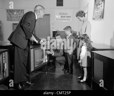 1960s FAMILY IN TV SHOWROOM TRYING SET WHILE SALESMAN WATCHES - Stock Photo