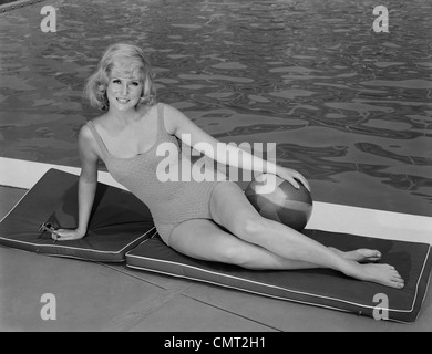 1960s SMILING BLOND WOMAN WEARING SWIMSUIT BY POOL POSING HAND ON BEACH BALL