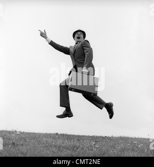 1960s BUSINESSMAN CARRYING A BRIEFCASE RUNNING YELLING AND JUMPING IN THE AIR OUTDOOR POINTING FINGER FORWARD - Stock Photo