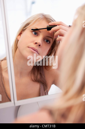 Woman standing in bathroom putting on make-up - Stock Photo