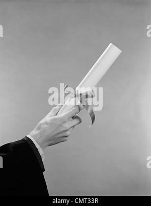 1950s 1960s MALE HAND HOLDING GRADUATION DIPLOMA - Stock Photo