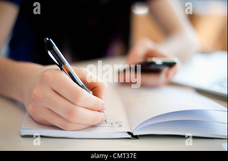 Close-up of human hand writing and holding mobile phone - Stock Photo