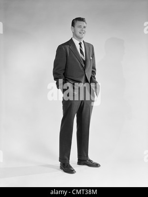 1950s 1960s PORTRAIT SMILING MAN STANDING WITH HANDS IN POCKETS WEARING SUIT AND TIE - Stock Photo