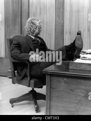 1930s STRAW MAN IN SUIT & TIE SEATED IN EXECUTIVE CHAIR WITH FEET PROPPED UP ON OFFICE DESK - Stock Photo