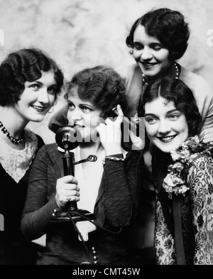 1920s GROUP OF FOUR WOMEN GATHERED AROUND CANDLESTICK PHONE - Stock Photo