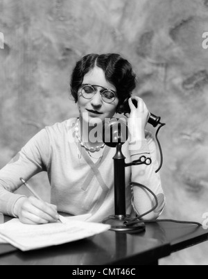 1920s WOMAN WEARING PINCE-NEZ GLASSES SITTING AT DESK TALKING ON CANDLESTICK PHONE AND WRITING - Stock Photo