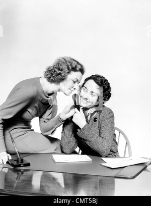 1930s TWO SMILING WOMEN OFFICE WORKERS TALKING INTO RECEPTIONISTS TELEPHONE SET SITTING AT DESK - Stock Photo