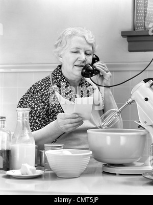 1940s WOMAN GRANDMOTHER HOUSEWIFE COOK IN KITCHEN WEARING APRON WITH FOOD MIXER READING INGREDIENTS LIST TALKING - Stock Photo